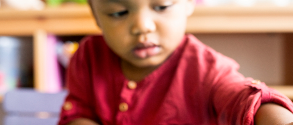 A baby boy in a red shirt playing with blocks.