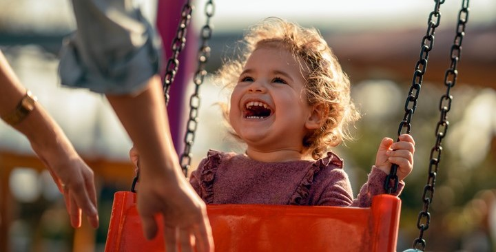 A toddler girl laughing while being pushed in a swing by her mother.