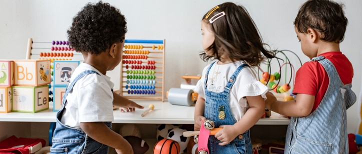 Three toddlers, standing up, playing with various toys in a classroom