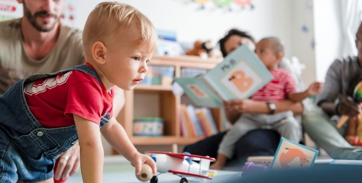 A little boy playing with a wooden ball in a classroom, with his dad behind him, and two other parents playing and reading to their children.